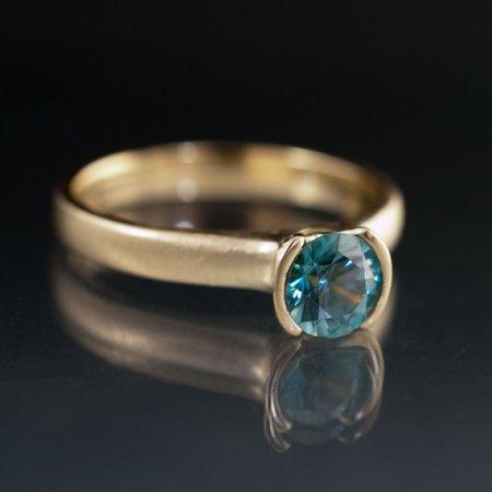 Nodeform Weddings Blue Zircon Half Bezel Solitaire Engagement Ring in Yellow Gold